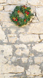 Decorative Christmas wreath on a vintage stone wall Royalty Free Stock Images