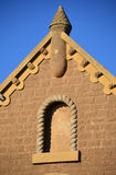 Decorative church roof peak. With blind gargoyles and ropework stone framed blank window Royalty Free Stock Images