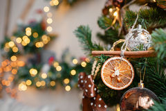 Decorative cinnamon and dried fruit close-up. Decorated Christmas tree on blurred, sparkling  fairy background Stock Photography