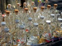 Decorative Clear Glass Bottles. Many small ornate shaped metal capped clear glass bottles, for sale at Athens central markets, Athinas Street, Greece. Many uses Stock Photography