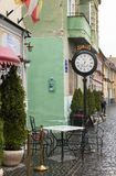 Decorative clock on the leg and table with chairs at the entrance to the cafe on the Cetatii street in a rainy day. Sibiu city in Royalty Free Stock Photos