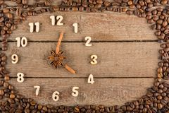 Decorative clock with wooden numerals and arrows made of cinnamon sticks, showing 4 o`clock, on a wooden background and a frame of. Coffee beans. Kitchen royalty free stock photo