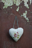 Decorative cloth heart textile hanging on old cracked wall. Decorative cloth heart textile hanging on old cracked wooden  wall Royalty Free Stock Image