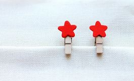 Decorative clothespins with red stars on bright cloth royalty free stock images