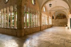 The decorative columns and arches of the corridors of the 13th Century Franciscan Monastery in Dubrovnik. The decorative columns and arches of the corridors of royalty free stock photo
