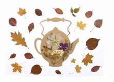 Decorative composition of handmade paper teapot and fall dry leaves on white background. Decorative composition of handmade paper teapot and fall dry tree leaves royalty free stock image