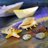 Decorative composition installation - smooth sea stones, sea salt, shells, starfish and paper boats on a blue background royalty free stock photos