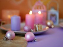 Decorative composition in a pink color from burning candles, decorative lanterns, oriental sweets on dishes, Christmas decor, ball royalty free stock image