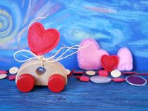 Decorative composition of a toy car and a heart made of felt on the background of pastel drawing, romantic decor on a blue wooden. Table, the concept of stock image