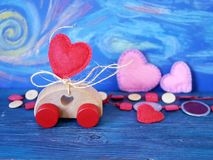 Decorative composition of a toy car and a heart made of felt on the background of pastel drawing, romantic decor on a blue wooden. Table, the concept of royalty free stock photography