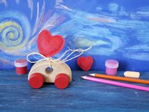 Decorative composition of a toy car and a heart made of felt, paints and pencils on the background of pastel drawing, the concept. Of congratulations on royalty free stock photo