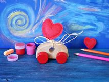 Decorative composition of a toy car and a heart made of felt, paints and pencils on the background of pastel drawing, the concept. Of congratulations on stock photos