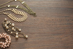 Decorative composition of women`s jewelry on wooden dark background. Flat lay. The view from the top. The concept of fashion and beauty royalty free stock photos