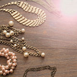 Decorative composition of women`s jewelry on wooden dark background. Flat lay. The view from the top. The concept of fashion and beauty stock photos