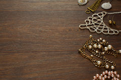 Decorative composition of women`s jewelry on wooden dark background. Flat lay. The view from the top. The concept of fashion and beauty royalty free stock photography