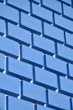 Decorative concrete wall with a relief similar to a large brick masonry painted in bright blue pain. T Stock Images
