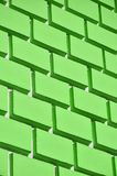 Decorative concrete wall with a relief similar to a large brick masonry painted in bright green pain. T Royalty Free Stock Image