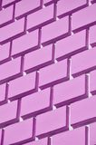 Decorative concrete wall with a relief similar to a large brick masonry painted in bright pink paint.  stock images