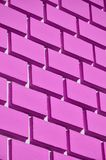 Decorative concrete wall with a relief similar to a large brick masonry painted in bright pink pain. T stock photography