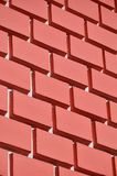 Decorative concrete wall with a relief similar to a large brick masonry painted in bright red pain. T Stock Images