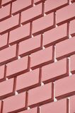 Decorative concrete wall with a relief similar to a large brick masonry painted in bright red paint.  stock photo