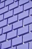 Decorative concrete wall with a relief similar to a large brick masonry painted in bright violet paint.  stock image