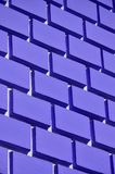 Decorative concrete wall with a relief similar to a large brick masonry painted in bright violet pain. T royalty free stock image