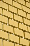 Decorative concrete wall with a relief similar to a large brick masonry painted in bright yellow pain. T Royalty Free Stock Photos