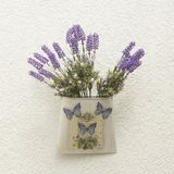 Decorative container with butterflies and lavender flowers. Vintage vase decorated with lavender flowers and butterflies on a white textured wall stock photos