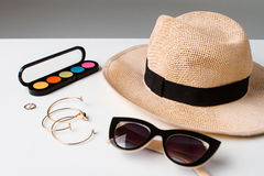 Decorative cosmetics accessories sunglasses and hat on white table. Stock Images