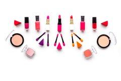 Decorative cosmetics pattern. Eyeshadows, rouge, applicators. lipstick, nailpolish on white background top view Royalty Free Stock Photography
