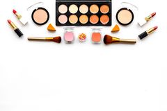 Decorative cosmetics pattern. Eyeshadows, rouge, nailpolish, brushes. lipstick on white background top view copyspace Stock Images