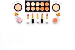 Decorative cosmetics pattern. Eyeshadows, rouge, nailpolish, lipstick on white background top view copyspace Stock Photos