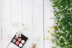 Fresh flowers, decorative cosmetics on a wooden background royalty free stock images