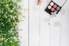 Fresh flowers, decorative cosmetics on a wooden background. Decorative cosmetics and wildflowers on a light wooden background royalty free stock photos