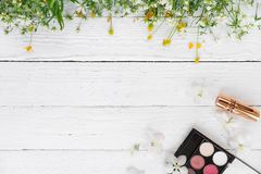 Fresh flowers, decorative cosmetics on a wooden background. Decorative cosmetics and wildflowers on a light wooden background royalty free stock photo