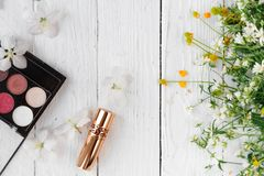 Fresh flowers, decorative cosmetics on a wooden background stock images