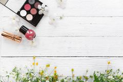 Fresh flowers, decorative cosmetics on a wooden background royalty free stock photography