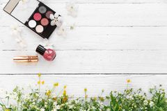 Fresh flowers, decorative cosmetics on a wooden background royalty free stock photos