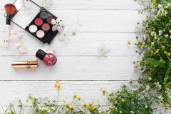 Fresh flowers, decorative cosmetics on a wooden background stock photo