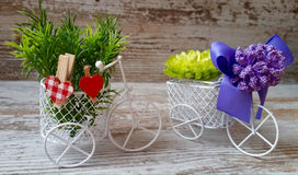 Decorative cozy bicycles with baskets, flowers, bow and wooden hearts Royalty Free Stock Photo