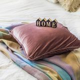 A decorative cozy pillow and the inscription HOME. In the home with a blanket royalty free stock photo