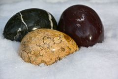 DECORATIVE CRYSTAL EGGS. Polished, egg shaped rocks are nestled in a bed of snow Royalty Free Stock Photography