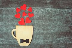Fathers day concept. Decorative Cup with bow-tie and hearts on dark wooden background. Copyspace royalty free stock photography