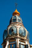 Decorative cupola. Architectural details of a cupola with round glass windows and weather vane on top Royalty Free Stock Photo