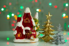 Decorative cute red house with gold and silver christmas trees on green sparkling background. Christmas / New year beautiful backgrounds stock photography