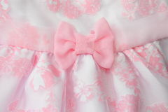 Decorative detail in the form of textile bow on children's dress. Royalty Free Stock Photography