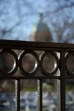 Decorative details of metal fence with a silhouette of a dome in Stock Photo