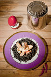 Decorative dish with black p. Black pasta with seafood on a plate purple Stock Photography