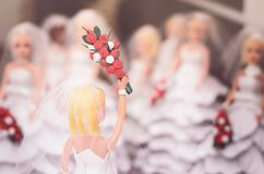 Decorative doll with a handcrafted white wedding dress holding h. Igh a bouquet of flowers ready to throw. Decorative wedding ornament Royalty Free Stock Photo